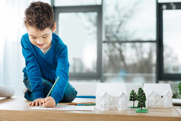 Creativity vibes. Pleasant adorable little boy sitting on the top of the table in the architect studio and drawing a picture with pencils