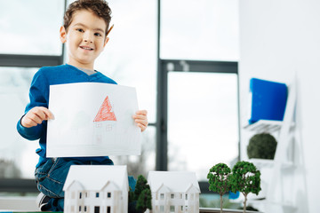 Young artist. Chubby little boy sitting on the top of the table full of house models and posing with a picture of a house, having drawn it by himself