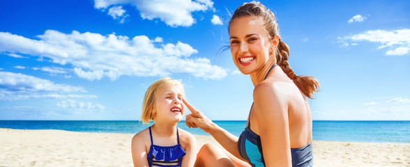 happy young mother and daughter on beach applying sun block