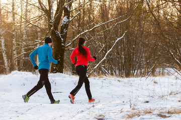 Picture from back of sports man and woman on morning run in winter