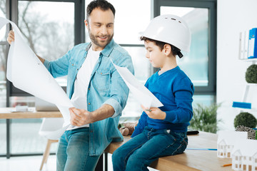 Skilled artists. Cute little boy in a white hard hat holding a picture while sitting on the table next to his father showing a blueprint to him