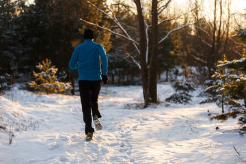 Picture from back of young athlete running through winter forest