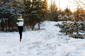 Picture of cheerful sportswoman in sneakers on morning run in winter forest