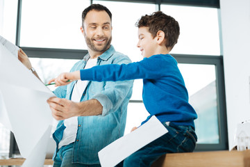 Look here. Cheerful little boy sitting on the table in the office and pointing at the blueprint in the hands of his father while smiling