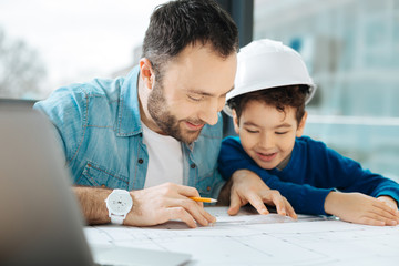 Little lesson. Charming young architect showing his son how to draw a blueprint while the boy in a white hard hat watching it attentively and with a smile