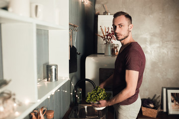 Portrait of smiling man. Guy in sport home clothes washing salad in the kitchen. Rustic color lifestyle photo of boy in loft interior.
