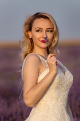 beautiful bride in lavender field, smelling a lavender flower, looking at sunset, after wedding, trash the dress, shooting, spring or summer