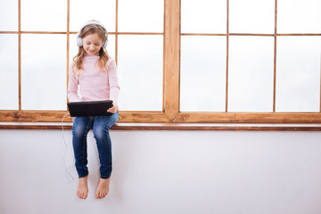 Relaxing. Beautiful happy fair-haired girl smiling and using her tablet and wearing headphones while listening to music and sitting on a windowsill