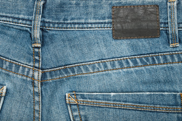 Jeans. Blue Pants Jeans With Blank Brown Label Textured Background Close Up.