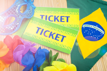Brazil tickets sitting next to Carnival mask and colorful flower lei on tropical background with Brazilian flag