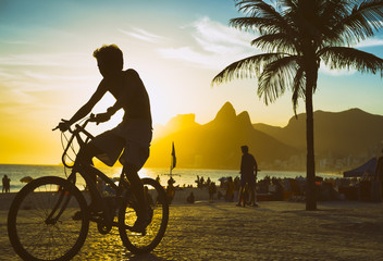 Foto op Plexiglas Rio de Janeiro Scenic sunset view of unrecognizable cyclist riding his bike along the Ipanema Beach promenade in Rio de Janeiro, Brazil