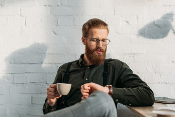 handsome bearded businessman holding cup of coffee and checking time