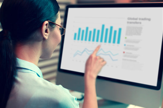 Important detail. The focus being on a pretty dark-haired young woman looking at the computer screen and pointing at a bar chart