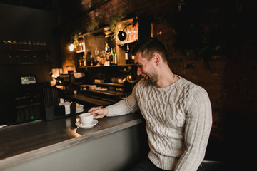 Man in cafe with cup of coffe. Lifestyle portrait of handsome boy in sweater. Rustic styling.