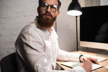 businessman writing something to notebook in office and looking away