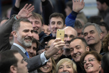 Spain's King Felipe VI takes a selfie with a group of farmers and workers during a visit to a dairy products company in Siero