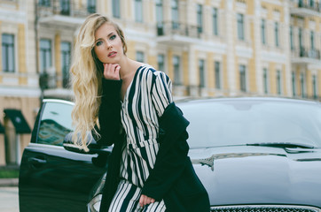 Beautiful fashionable blonde with long hair in a black coat posing sitting on a black car in the city. Fashion photo. Street photos.