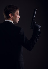 Photo from back of gangster man in leather gloves with gun