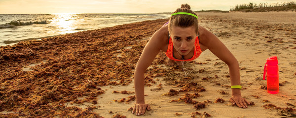 healthy woman in sport clothes on beach doing pushups