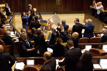 Ushers scuffle with members of the Joint Arab List who are holding signs in protest ahead of U.S. Vice President Mike Pence's address to the Knesset, Israeli Parliament, in Jerusalem