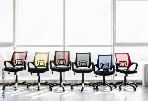 colorful office chairs. Colorful Office Chairs Standing In A Row At Big Window. Concept.