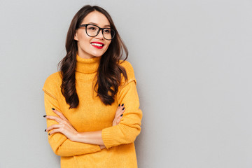 Smiling brunette woman in sweater and eyeglasses with crossed arms