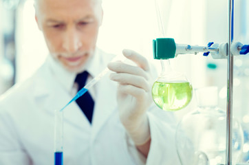 Chemical experiment. Selective focus on a laboratory glassware fixed on a metal stand while a mature gentleman conducting chemical experiment in the background.