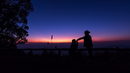 The silhouette of women and men is watching the sunset happily.