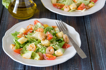 Caesar salad with shrimps on a wooden background