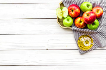 Apple cider vinegar in bottle among fresh apples on white wooden background top view copy space