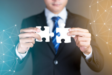 Businessman hands connecting puzzle pieces representing the merging of two companies or joint venture, partnership, Mergers and acquisition concept.