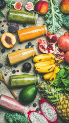 Flat-lay of colorful smoothies in bottles with fresh tropical fruit and vegetables on concrete background, top view, vertical composition. Healthy, vegetarian, detox, dieting breakfast food concept