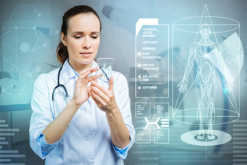 Unbelievable. Smart skilled experienced doctor feeling impressed by the fast development of modern technologies while looking at the amazing transparent gadget in her hands