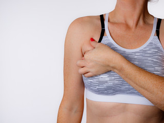 Woman in Sports Bra Pinching Arm Fat on a White Background