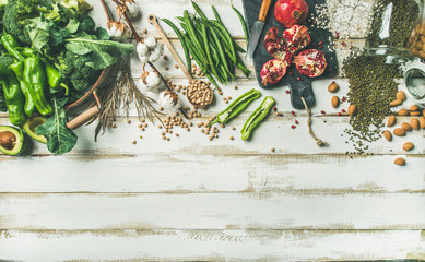 Winter vegetarian, vegan food cooking ingredients. Flat-lay of vegetables, fruit, beans, cereals, kitchen utencil, dried flowers, olive oil over white painted wooden background, top view, copy space