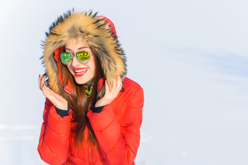 Attractive woman with mirror green sunglasses and red jacket in winter. Active and joyful outdoor recreation. Winter time resort, leisure outdoors, sport and people concept - happy young woman