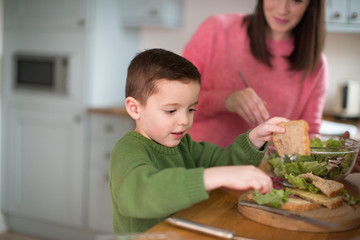 Boy making a sandwich with Mother helping