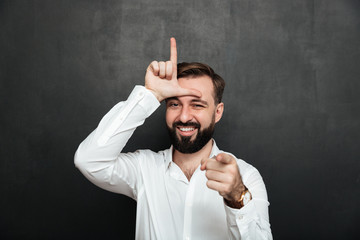 Portrait of sarcastic man showing loser sign on his forehead and pointing on camera with smile, mocking or humiliate over graphite wall