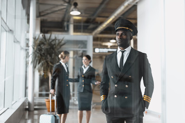 thoughtful young pilot in airport with stewardesses before flight Wall mural