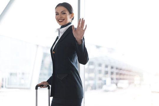 attractive young stewardess with suitcase waving at camera in airport