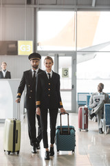 young male and female pilots walking by airport lobby with suitcases