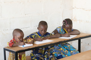 Three beautiful African Children in School Taking Notes during Class