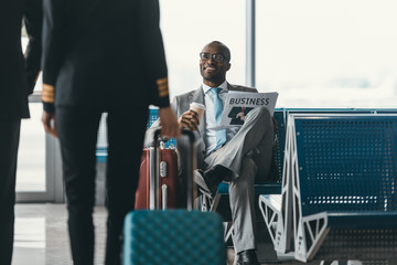 handsome young businessman looking at female pilot passing by while wait for flight at airport lobby