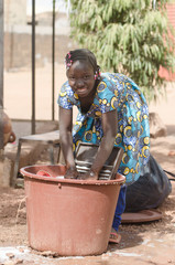 Little African Girl Working at Home Washing Clothes Outdoors
