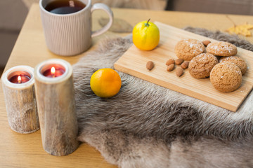 Fototapete - cookies, lemon tea and candles on table at home
