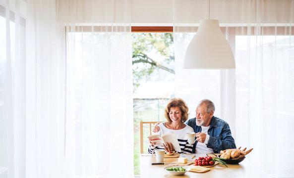 Senior couple eating breakfast at home.