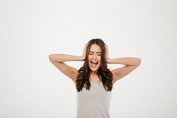 Image of Angry brunette woman screaming and covering her ears