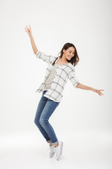 Full length image of Cheerful brunette woman in shirt dancing