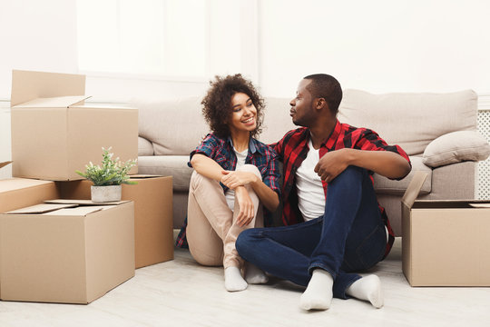 Young balck couple unpacking moving boxes