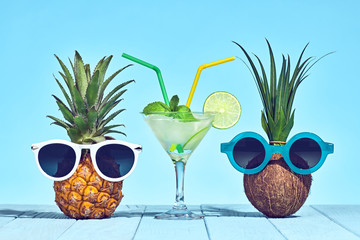Two Hipster Fruits in Trendy Sunglasses, Cocktail on Beach. Tropical Pineapple and Coconut. Bright Summer Color.Fashion Style. Creative Art. Fun Summer party Mood